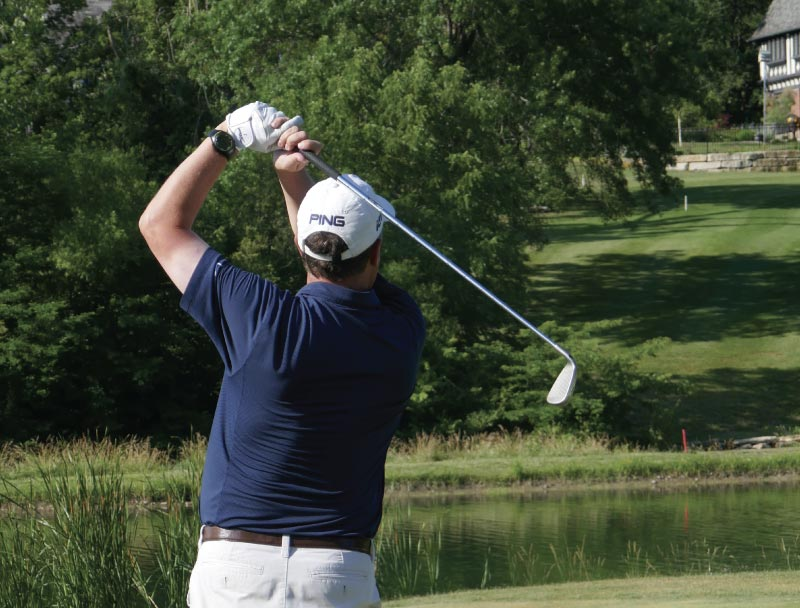 Man in a white hat, blue polo short, and khaki pants swinging a golf club at a golf course.