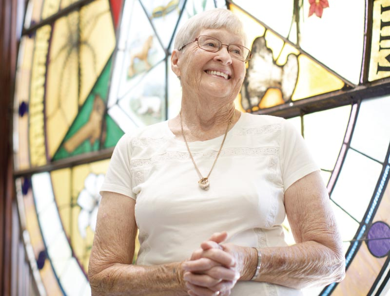 Elderly woman in white shirt with hands clasped standing in front of stained glass window.
