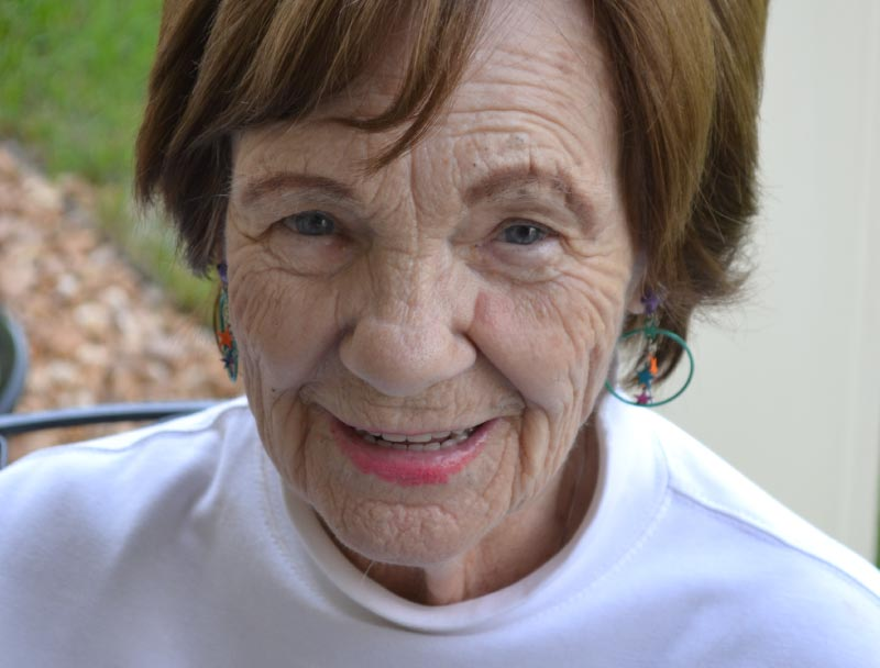 Elderly woman smiling with brown hair with a white shirt on.