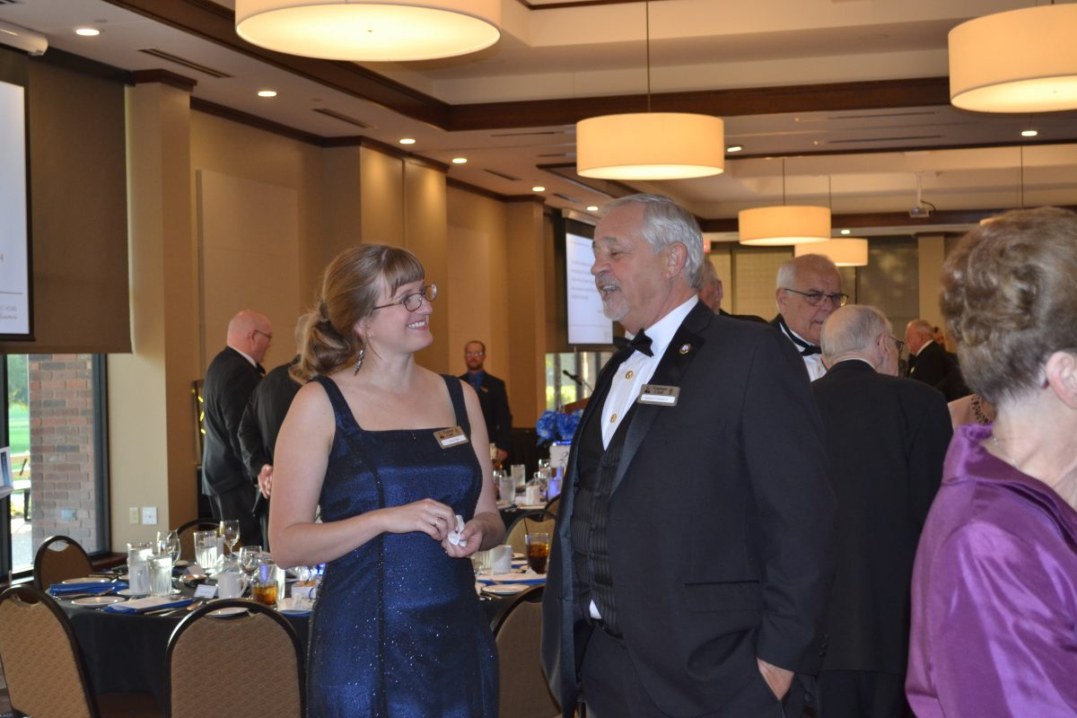 Man in a tuxedo talking to a woman in a blue evening dress.