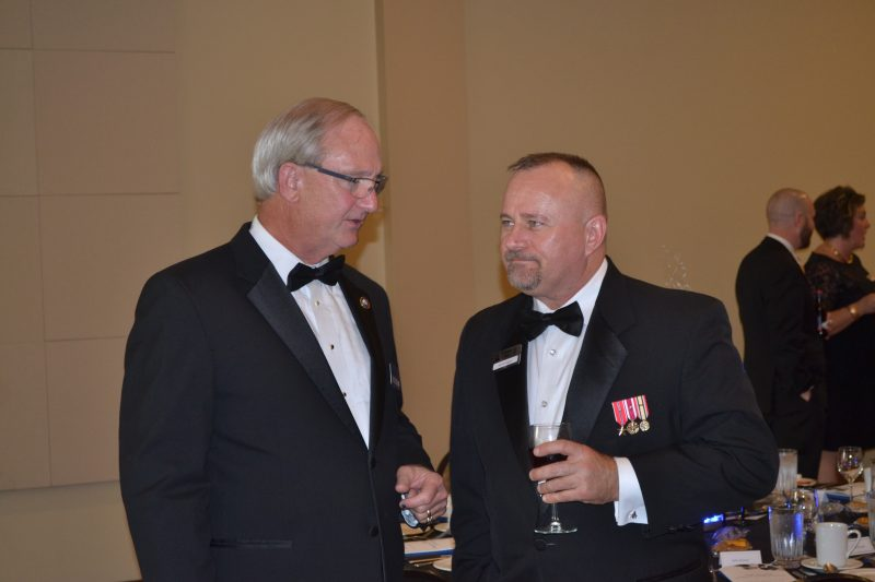 Two men in tuxedos with drinks at a nice event.