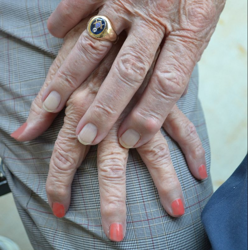 Wrinkled hands of an old man and woman. Man is wearing a gold ring with the Masonic crest on it, the woman has her nails painted pink.