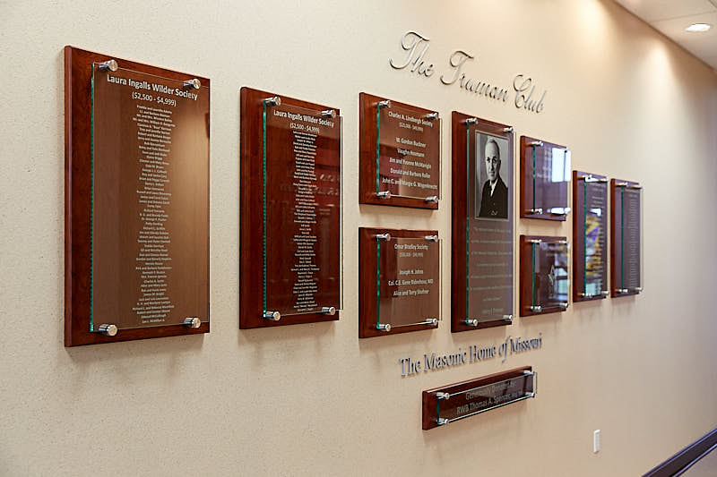 Wall with various wooden plaques showing donors and members of the Truman Club.