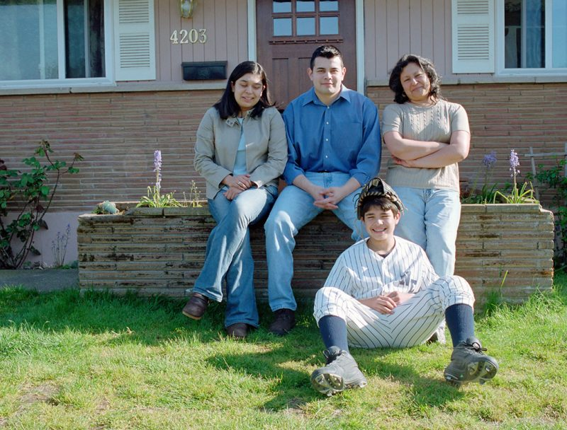 Family of four sitting in front of home on the lawn.