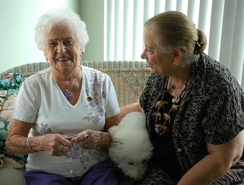 Two women sitting on a couch laughing, one woman is elderly, the other is a social worker helping her out.
