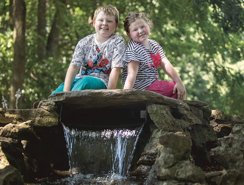 Boy and girl sitting on a rock in the forest, water flowing below